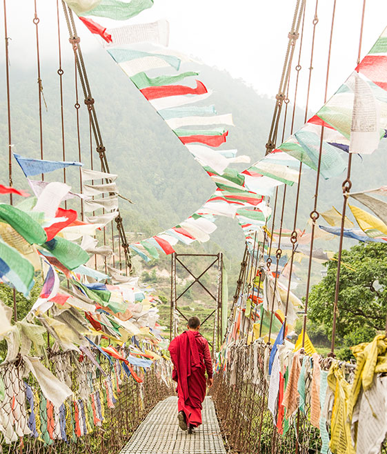 Impact tourism. Bhutanese Monk crosses one of the many prayer-flag-covered bridges